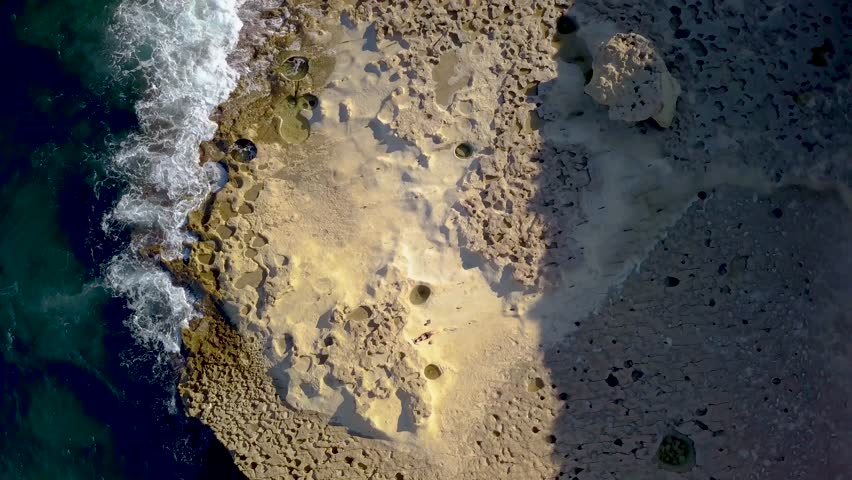 Aerial view of a beach in Malta, near st peter's pool. Water falling to the rocks...