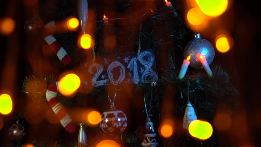Plate numbered 2018 on a Christmas tree among toys and yellow electric lights, New Year's background. | Shutterstock HD Video #33030625