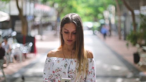 Beautiful Blonde Girl walks on the street and video chatting. European street. Girl travels concept.