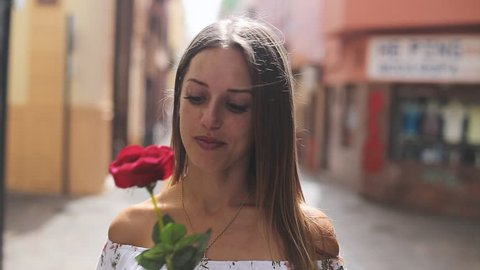 Cute Blonde girl dating and holding red rose in her hand. Point of view. Looking to the camera.