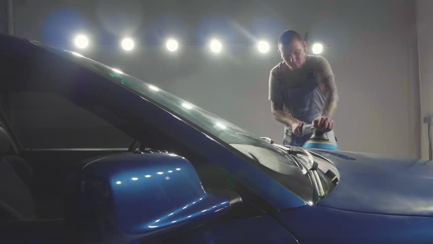 Master with tattooing hands polishes the deep blue sport car via polish mashine in a car workshop, slow motion