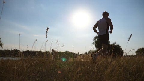 Young man running outdoor with his dog. Labrador or golden retriever jogging with his male owner at nature. Healthy active lifestyle. Slow motion