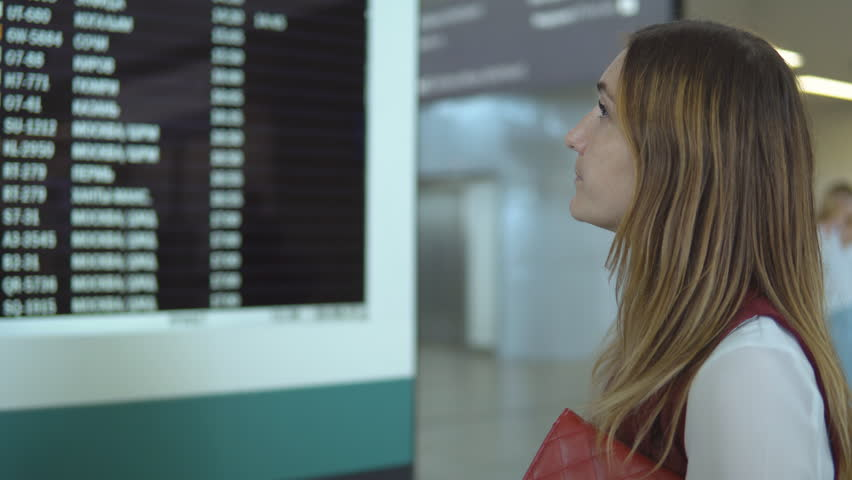 Pretty young female stands near of scoreboard with the notice and choice number flight. | Shutterstock HD Video #33056167