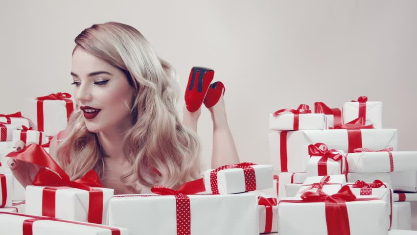 Happy beautiful young woman lies among the gift boxes over white background. Isolated in a studio on white background.   Shutterstock HD Video #33058114