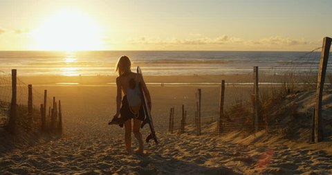 Side View Footage of Beautiful Young Woman Carrying Surfboard Walking Towards the Sea. Girl Has Blonde Hair and a Backpack.The Beach is Empty and Sun is Setting.  Shot on RED Epic 4K UHD Camera.