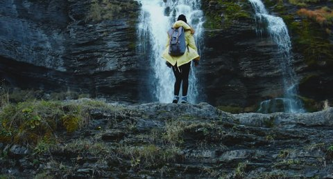CRANE SHOT Caucasian female hiker in yellow raincoat wearing backpack enjoys the view of a beautiful waterfall in French Alps. 4K UHD RAW edited footage