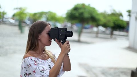 Cute blonde tourist girl is filming streets and sightseeing in Santa Cruz de Tenerife, Canary Islands, Spain. The girl travels concept.