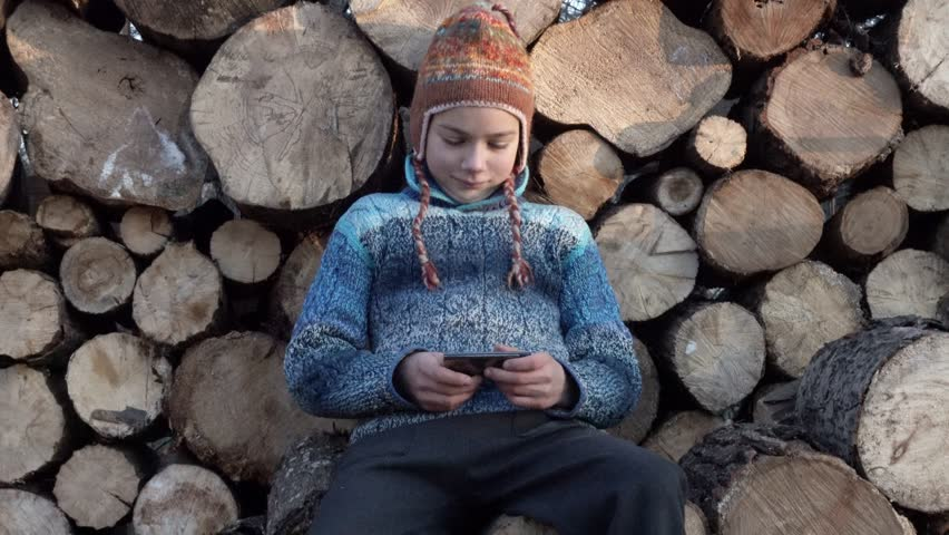 The boy is playing on the smartphone and hiding it behind his back. Portrait of a child on the background of firewood playing on a smartphone.  | Shutterstock HD Video #33094117