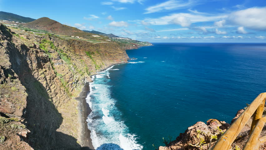 Timelapse sequence of tall waves at Playa de Nogales beach in La Palma, Spain. High angle view from an observation point on the cliff with some tourists running around in 4K resoultion. | Shutterstock HD Video #33102499