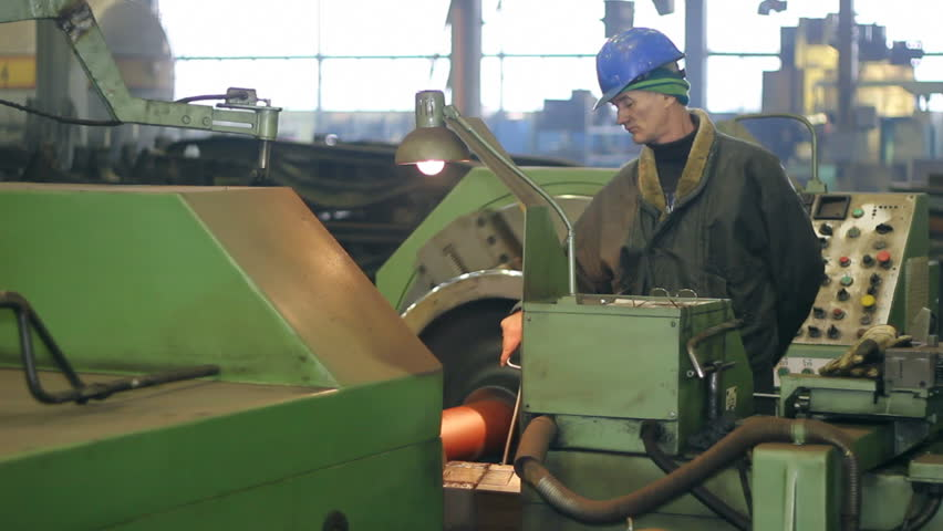 Worker on a machine, processing steel on a lathe in factory