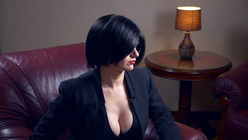 Hot brunette in round sunglasses, sits in a chair and shows a sheet with the inscription sex and love. 4k, slow motion | Shutterstock HD Video #33120040