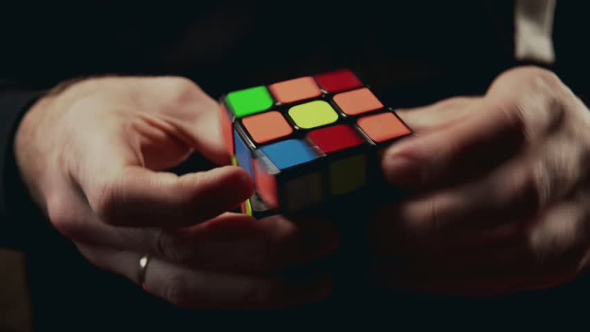 Minsk, Belarus - NOVEMBER 20, 2017: Boys hands solving Rubik's Cube 3x3x3 at dark background. Rubics cube is the world's top-selling puzzle game and one of the world's best-selling toys in 4k
