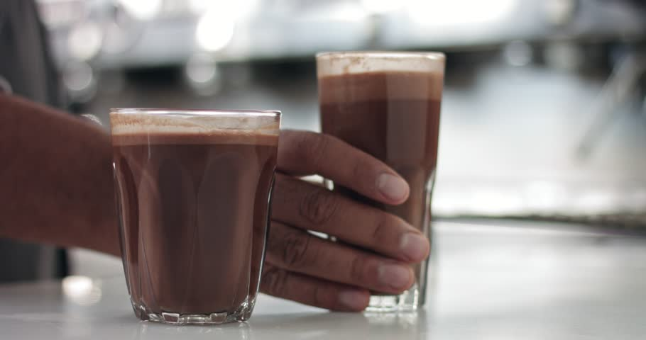 Close up of a barista in an industrial looking cafe making hot cocoa drinks in glass tumblers