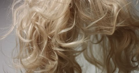 Close up video of blowing out long wavy blond woman's hair on white background