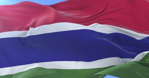 Gambian flag waving at wind in slow in blue sky, loop