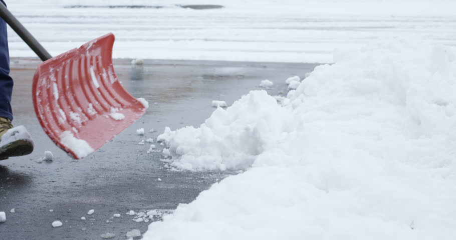 Man shovels driveway after first snowfall of the season | Shutterstock HD Video #33188950