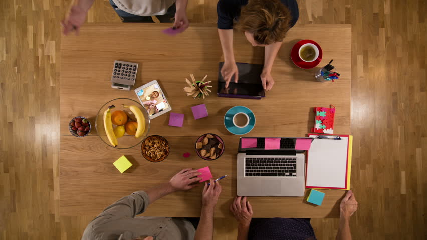 Timelapse view from above of a desk with two women and two men working together  | Shutterstock HD Video #33202588