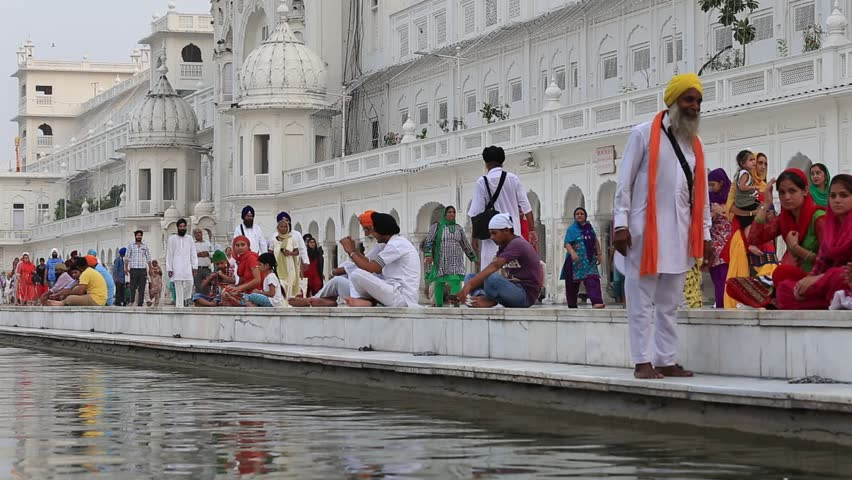 AMRITSAR, INDIA - SEPTEMBER 27, 2014: Unidentified Sikhs and indian people visiting the Golden Temple in Amritsar, Punjab, India. Sikh pilgrims travel from all over India to pray at this holy site