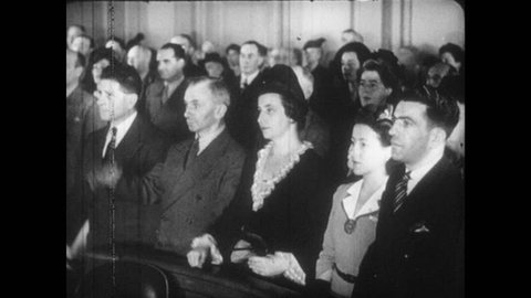 1940s: Men and women in courtroom raise right hands. Statue of Liberty.