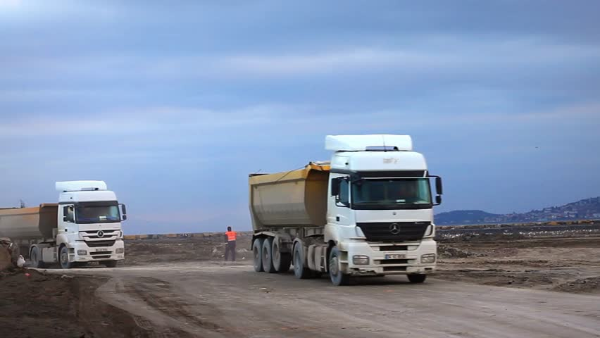ISTANBUL - DEC 30: Heavy duty dump trucks work for formation of new land by filling the sea at Maltepe Coast on December 30, 2012 in Istanbul. Transfer camions running to haul such as gravel or rock.
