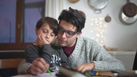 Big brother helping a little schoolboy kid or his son studying and doing homework at Christmas time. Educational school matter.
