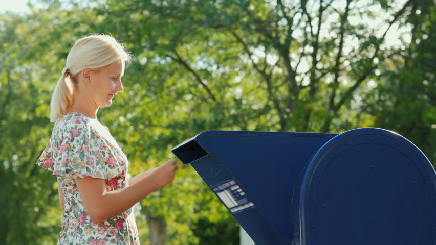 A woman in a summer dress is throwing a letter in a drawer near the post office | Shutterstock HD Video #33250141
