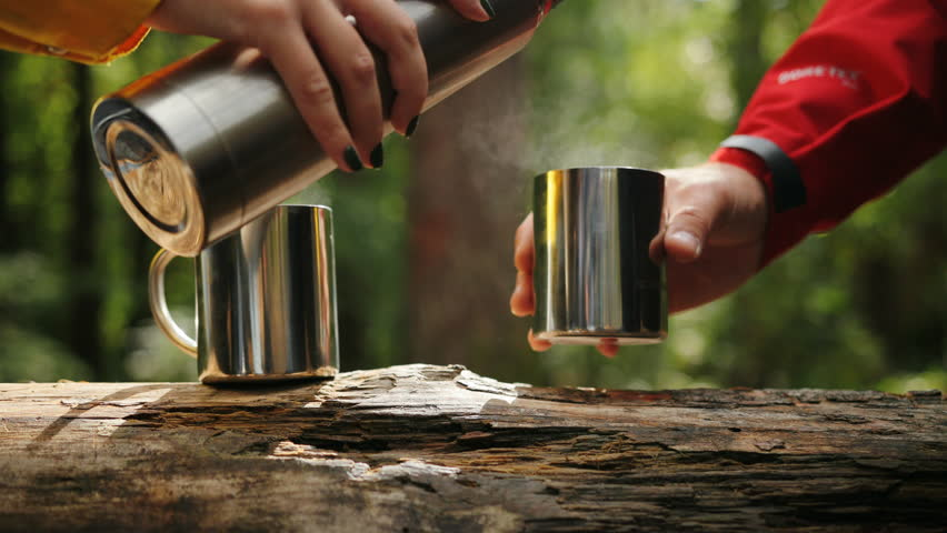 Close up of the female hand pouring a tea from a thermos in the cups which being holded by male hand. Forest background. Outside