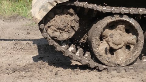 Close up dirty caterpillar tracks on military tank moving on road. Slow motion caterpillar tracks on war tank driving on muddy road