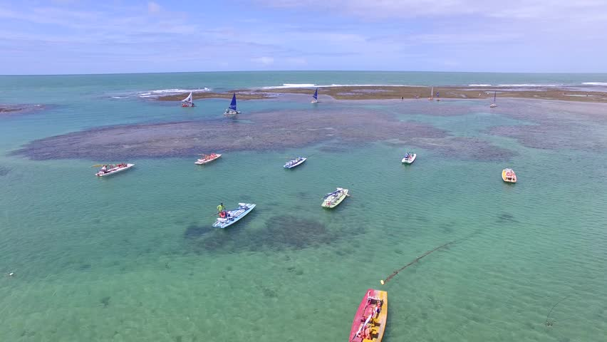 Aerial view over crystal clear waters and coral reef barriers, severals sailing boats in Porto de Galinhas beach - Pernambuco, Brazil
