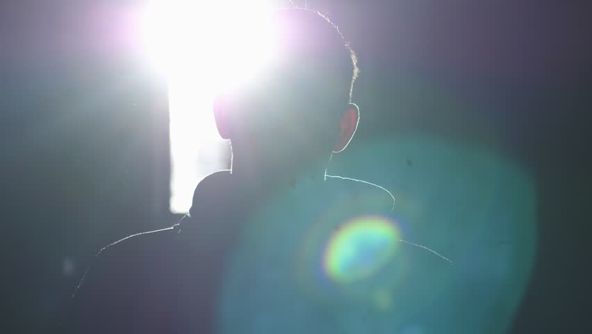 Silhouette of man standing by large window looking over the sun with lense flare effects. 3840x2160 | Shutterstock HD Video #33282280