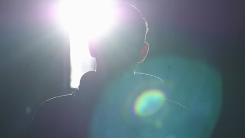 Silhouette of man standing by large window looking over the sun with lense flare effects. 3840x2160