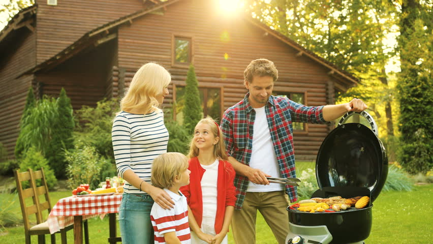 Happy Parents With Children Near Barbecue In The Green Yard Wooden House Outdoors