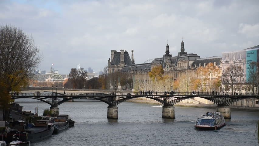 """Paris, People walking on """"Pont des Arts"""" in front of the Louvre Museum while boat full of tourists navigates on the Seine River , France"""