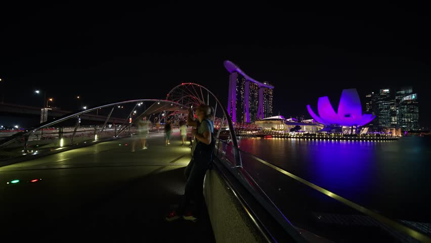 Singapore - November 27, 2017: Timelapse footage of Helix Bridge in Marina Bay Sands Singapore with ArtScience Museum and Marina Bay Sands Hotel view at night. Shot in 4k resolution #33334510