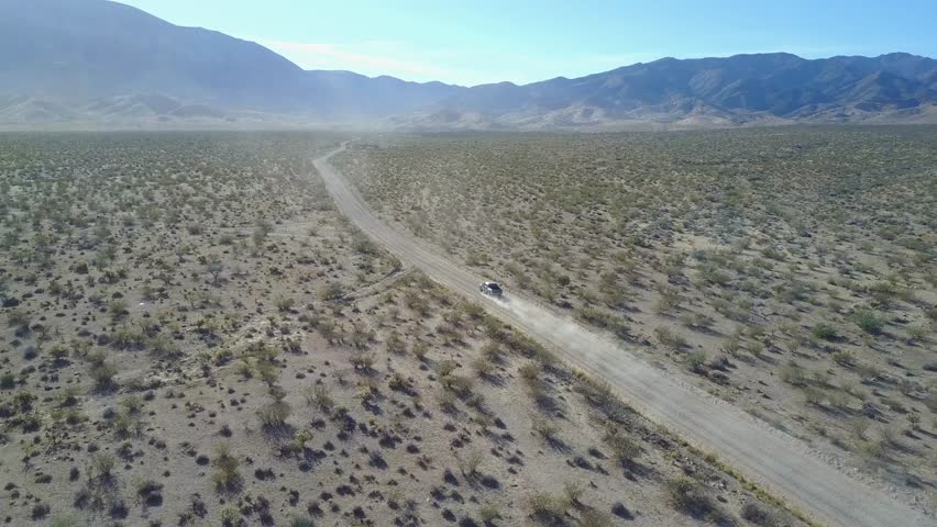 Truck driving on dusty desert road in bright sunshine, distant follow into sun.  Filmed outside Lime Kiln Canyon in North West Arizona near Mesquite, Nevada.