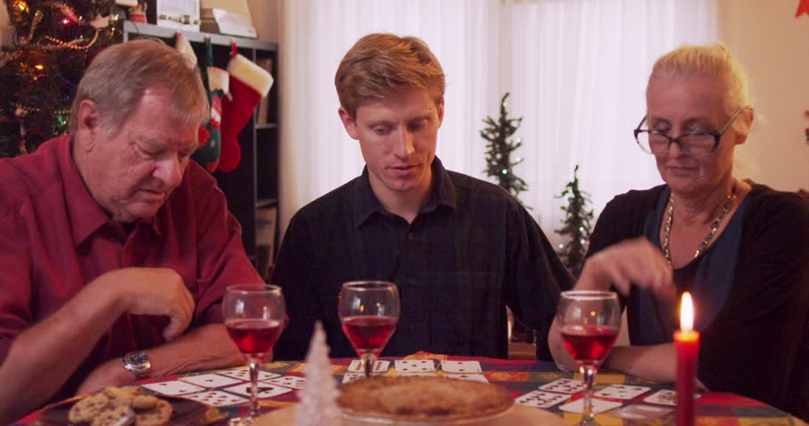 Grandparents and grandson playing cards at family dinner over holidays - slow motion | Shutterstock HD Video #33362050