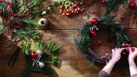 Overhead. Christmas time. On the wooden table, woman's hands make a crown for the festive season. branches of fir, berries, balls and rope to decorate it. Camera travelling