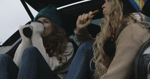 two travelling girls (women, sisters, siblings, twins, friends) having a break in the car trunk, drinking hot beverage from thermos (coffee, tea), eating cookie.