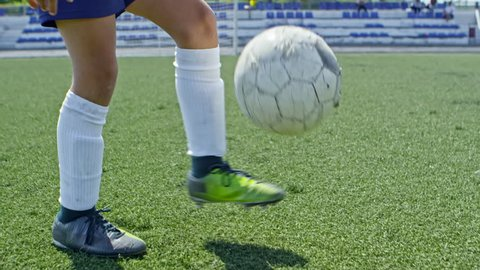 Tilt up with slow motion of blond boy from junior soccer league juggling ball on leg in outdoor playing field on sunny summer day