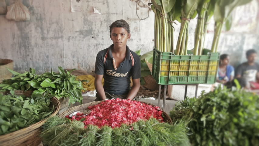 A wide shot of poor young boy selling flowers in the flower market