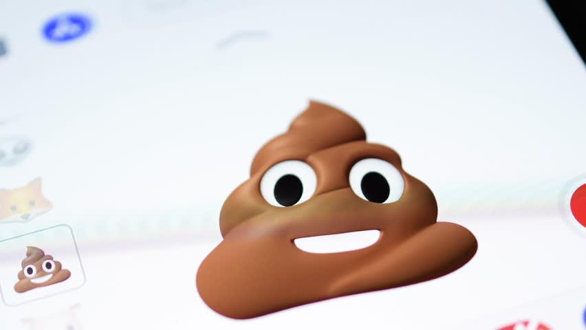 PARIS, FRANCE - NOV 4 2017: Shit Poop 3d animoji emoji generated by Face ID facial recognition system with different face emotion close-up of the new Apple iPhone X 10 Display - tilt-shift lens used