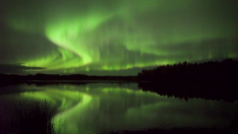 Realistic real-time (not a timelapse) aurora borealis (northern lights) dancing over lake with reflections in Alaska