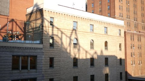 Establishing shot of bricked building in large downtown area