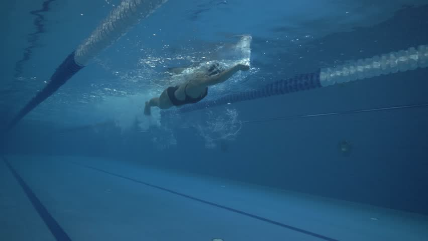 Woman floating crawl stroke in swimming pool underwater view. Close up female swimmer swims crawl stroke on swimming path in transparent water pool 60 fps
