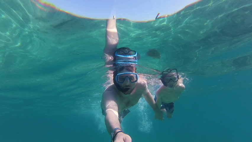 Folkekære Father and son with fins, mask, snorkel and a selfie stick swimming DO-29