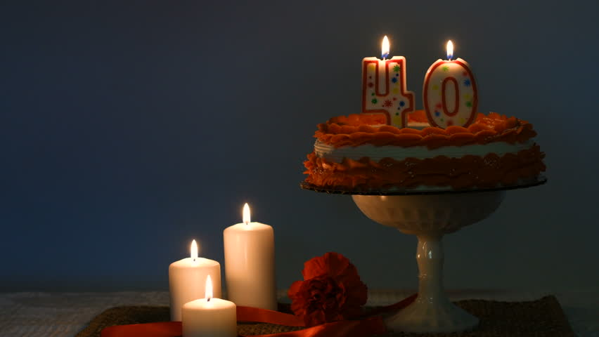 Frosted Cake With 40 Candle Lit On Top And Decorations