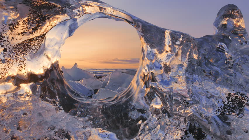 Sunrise on ice ocean - original frame idea, view from crystal clear ice to sea waves 60fps. Calmness atmosphere of winter Iceland morning.