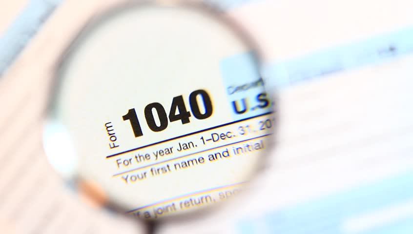 Magnifying glass on 1040 individual income tax return document.