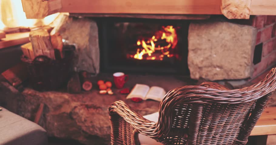 Warm Cozy Fireplace With Real Wood burning in it. Magical atmosphere. Cup of hot drink and book ready for evening relax. Cozy winter concept. Christmas and travel background with space for your text. #33513400
