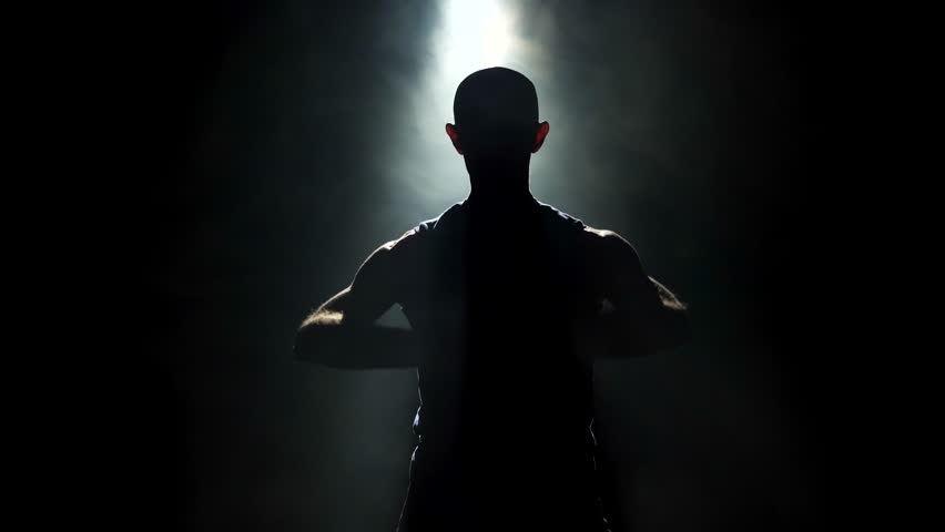 Close up of a silhouette of a man stretching in a darkened room with a single ray of light coming from a spotlight. He is lifting his arms up over his head, stretching them to each side